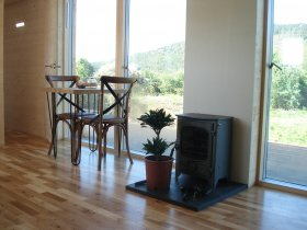 An image showing the interior and wood burning stove at Loch Ken Eco Bothies self catering accommoda